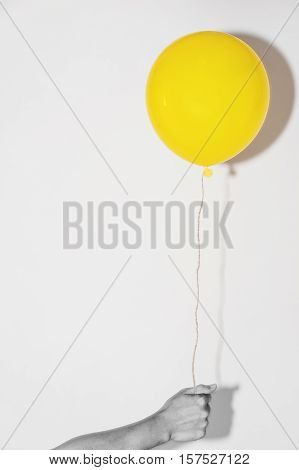 Hand holding yellow balloon on white wall with shadow reflection