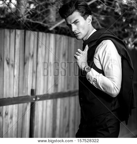 Black-white outdoor portrait of elegant handsome man in classical vest near wooden fence.