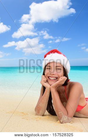 Merry Christmas santa hat woman on beach vacation holiday season. Happy Asian multiracial woman smiling wearing santa hat lying down on beach relaxing on winter travel vacation. Cute girl sunbathing.