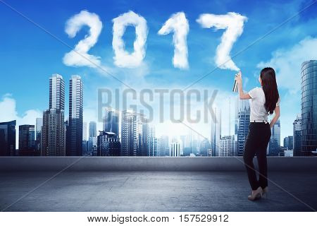 Business Woman Spraying White 2017 Year Cloud Shape