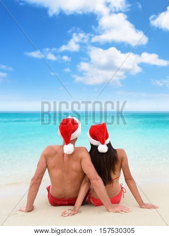 Christmas beach vacation holidays couple relaxing sitting down on white sand looking at turquoise ocean view in tropical travel destination. Couple from behind together sunbathing with santa hat.