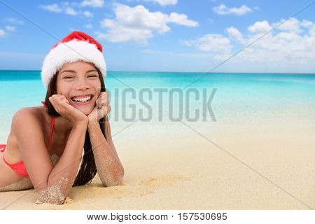 Merry Christmas background concept for holiday season. Happy Asian woman on tropical beach in santa hat lying down in sand texture with ocean copy space for travel vacation. Cute girl sunbathing.