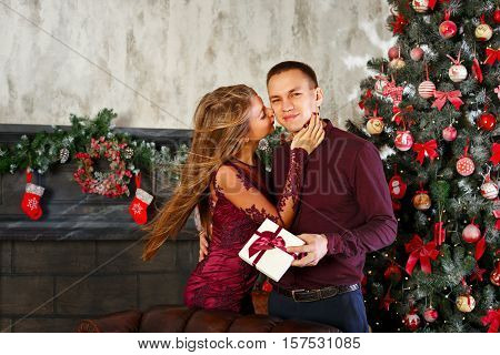 Loving couple and Christmas. Girl gives a kiss and a Christmas gift to her boyfriend. In the background a beautiful Christmas tree.