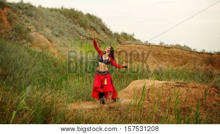 Oriental Beauty dance with a sword. Tribal style. Lovely girl in costume dancing outdoors. Sand dunes. Nomads.