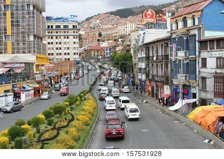 La Paz Bolivia - November 19 2016: Cars driving on highway with landscaped median strip and buildings in La Paz Bolivia on November 19 2016.