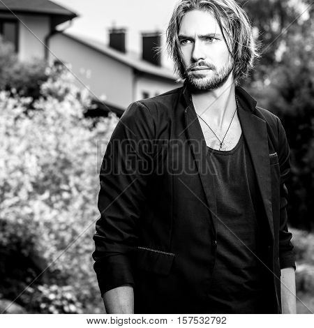 Black-white outdoor portrait of elegant long hair handsome man.