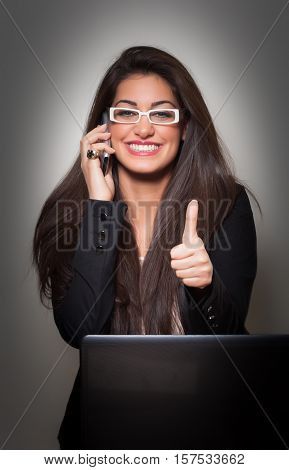 Successful Smiling Young Businesswoman wearing white glasses talking to phone