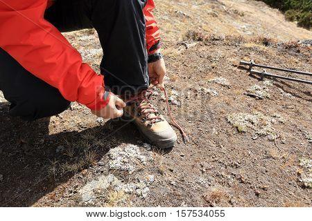 hiker tying shoelace on himalaya mountain trail
