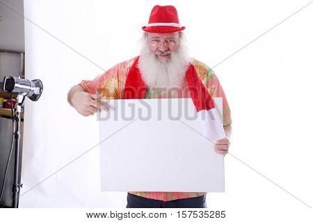Hipster Santa Claus with a blank white sign posing in a Photo Studio against a white background with Photographer Modeling Lights behind him. With room for your text