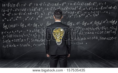 A businessman standing back to us with the drawing of a light bulb on his back looking at the blackboard with a lot of mathematical formulas on it. Mathematical calculating. Solving equations. Having ideas. Education.