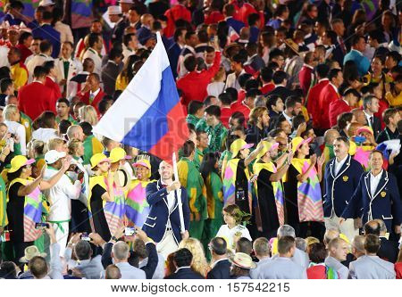 RIO DE JANEIRO, BRAZIL - AUGUST 5, 2016: Volleyball player Sergey Tetyukhin carrying the Russian Federation flag leading the Russian Olympic team in the Rio 2016 Opening Ceremony at Maracana Stadium