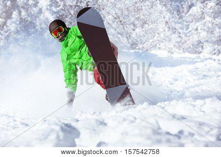 Active snowboarder rides in powder. Snowboarding extreme