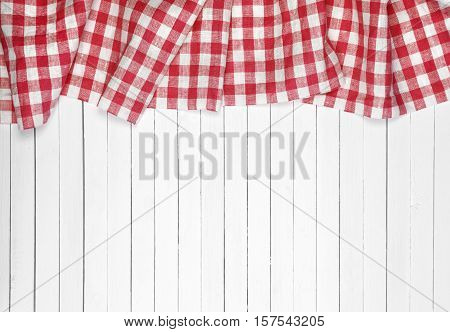Red checkered tablecloth on a light wooden table top view