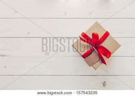 Brown Gift Box With Tag On Wooden Background. Vintage Gift Box On Wooden Background. Gift Box With R