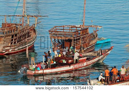 STONE TOWN, ZANZIBAR, TANZANIA - OCTOBER 31, 2014: Fishermen working on wooden fishing boats in the busy Stone Town harbor