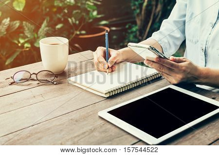 Female Hand With Pencil Writing On Notebook. Woman Hand Holding Phone With Pencil Writing On Noteboo