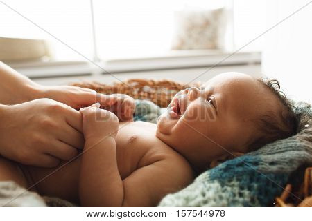 Baby smiling at mother, close-up. Adorable newborn child looking up at mother and holding her hands. Love, innocence, cuteness concept