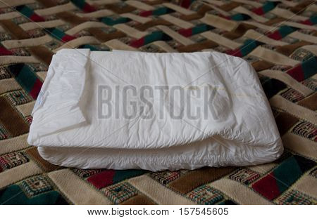 Folded disposable diaper for adults. Nursing care for the bedridden. Hygiene incontinence.