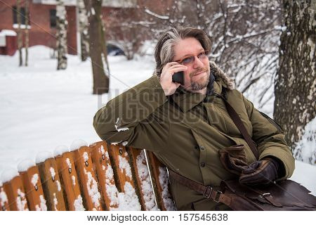 Man In A Winter Coat Sitting On A Bench, Call On The Phone