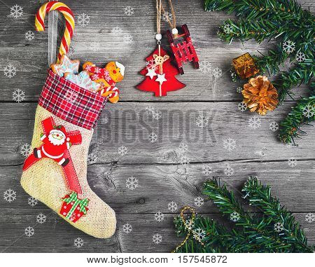 Christmas sock with presents. Christmas decoration stocking and toys hanging over gray rustic wooden background. The socks of burlap Christmas sweets gifts cakes. Top view