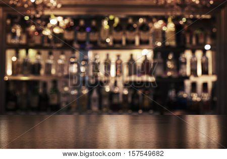 Empty wooden bar counter with defocused background of restaurant bar or cafeteria and copy space