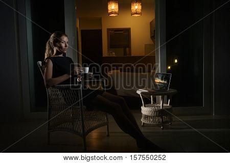 Woman drinking coffee in hotel terrace