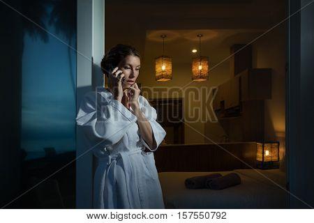 Woman talking on phone relaxing in luxury resort hotel