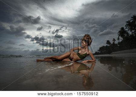 Young adult  girl sitting on tropical beach in sunset