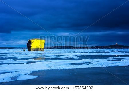 Night ice fishing. Yellow fishing shelter on the ice at night Nida Lithuania