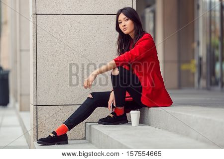 Confident asian businesswoman smiling in the city. Serious beautiful mixed race Asian Caucasian young woman in casual red suite outdoor sitting on steps of building with coffee cup. Next generation