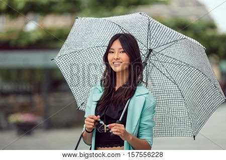 Asian girl city portrait. Woman smiling outside with umbrella in casual business suite looking at camera. Beautiful young mixed race Asian Caucasian woman.