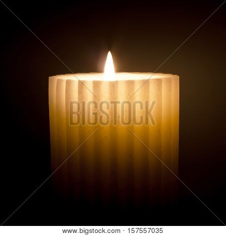 Isolated burning white candle on dark background