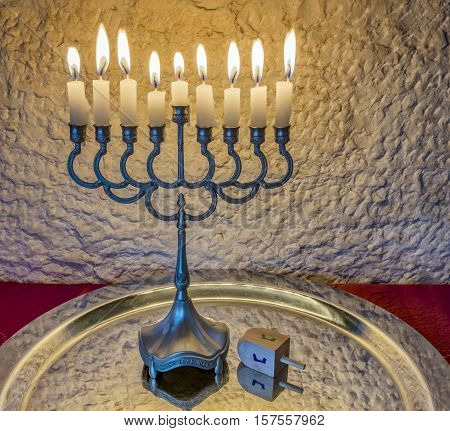 Menorah with the glitter lights of candles and wooden dreidel are traditional Jewish attributes and symbols for Hanukkah holiday. Selective focus. Image toned for retro style