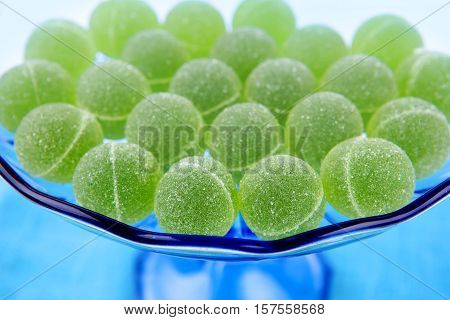Sweet jelly flavor fruit green dessert. Round candies in blue stand.
