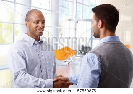 Interracial businessmen shaking hands in business hall, smiling,