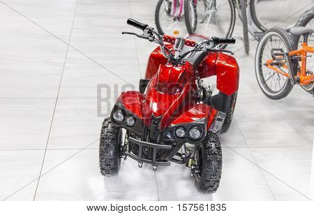 Close view of childs electric red four wheel motorcycle