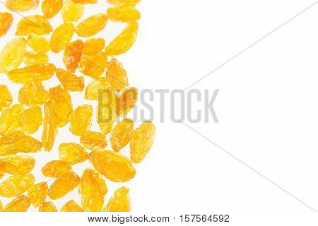 Raisins yellow closeup on white background. Isolated. Decorative border of shiny golden yellow raisins dried fruit. Dried fruit for vegetarian.