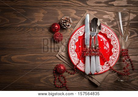 Christmas empty plate and silverware on wooden background as design element for menu, top view with copy space