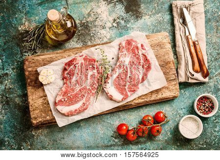 Two raw fresh marbled meat black angus steak ribeye and seasonings on blue concrete background. Top view