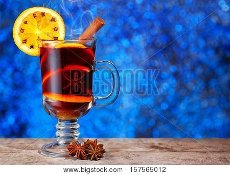 Hot mulled wine with cinnamon stick orange slice and anise stars on wooden table with new year bokeh background. Christmas mulled wine with spices. Mulled wine with front of bright blue bokeh lights background with copy space. The idea for postcard