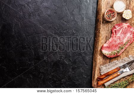 Raw fresh ribeye steak on cutting board on black stone background. Top view