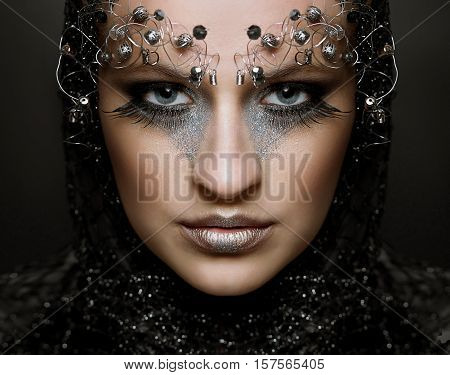Fashion portrait of a beautiful woman with long eyelashes and piercing eyes. The idea of an unusual and original make-up for make-up artists.