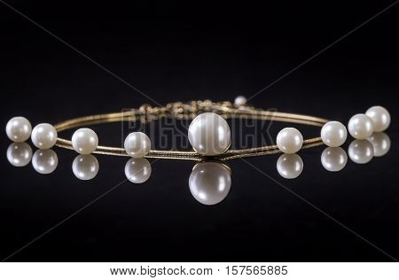 White pearls necklace on black background. Focus on the big pearl!