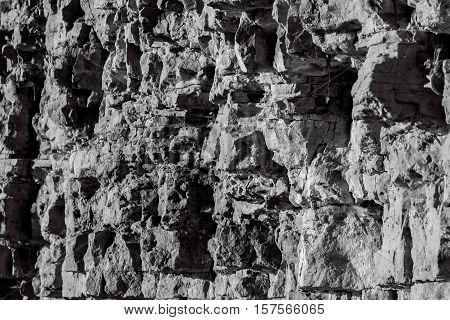 stone ruined wall collapses in parts, autumn maple leaf hangs on the rocks caught on the web, sunny evening, wall of natural material, the fall looks and background, a stone is destroyed, black and white photo