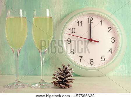 A photo of two flute glasses of sparkling wine with a pine cone, a clock about to strike midnight, and copyspace