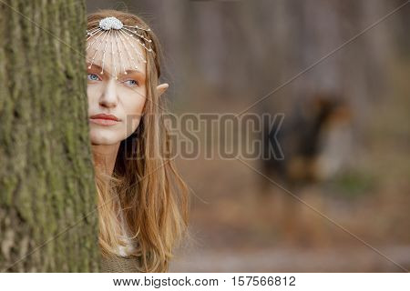 A portrait of a beautiful woman with elf ears and diadem in the forest.