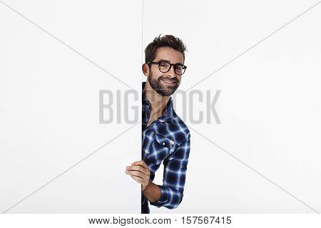 Portrait of man smiling in checked shirt white studio