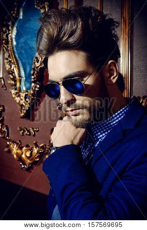 Portrait of a well-dressed imposing man in sunglasses standing in apartments with luxurious classic interior. Men's beauty, fashion. Hair styling, barbershop.