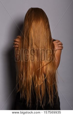 Gloomy Depressed Woman In Black Clothes With Long Blonde Hair Covering Her Face Embrace Herself With