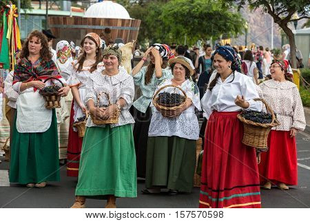 FUNCHAL MADEIRA PORTUGAL - SEPTEMBER 4 2016: Group of women in traditional costume carrying a basket full of grapes durnig parade of Madeira Wine Festival in Funchal.Madeira Portugal